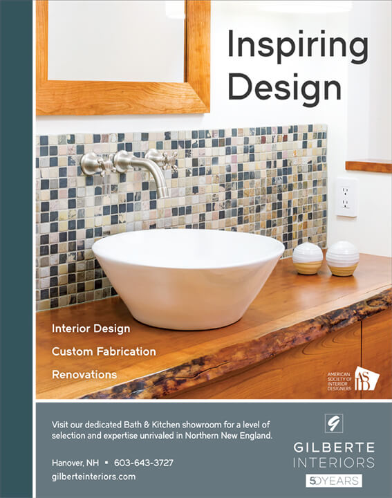 A modern bathroom counter incorporating small, colorful tiles between the wood-framed mirror and the wood counter. Text reads: Gilberte Interiors 50 Years Inspiring Design: Interior Design, Custom Fabrication, Renovations. Visit our dedicated Bath & Kitchen showroom for a level of selection and expertise unrivaled in Northern New England, American Society of Interior Designers, Hanover, NH 603-643-3727, gilberteinteriors.com