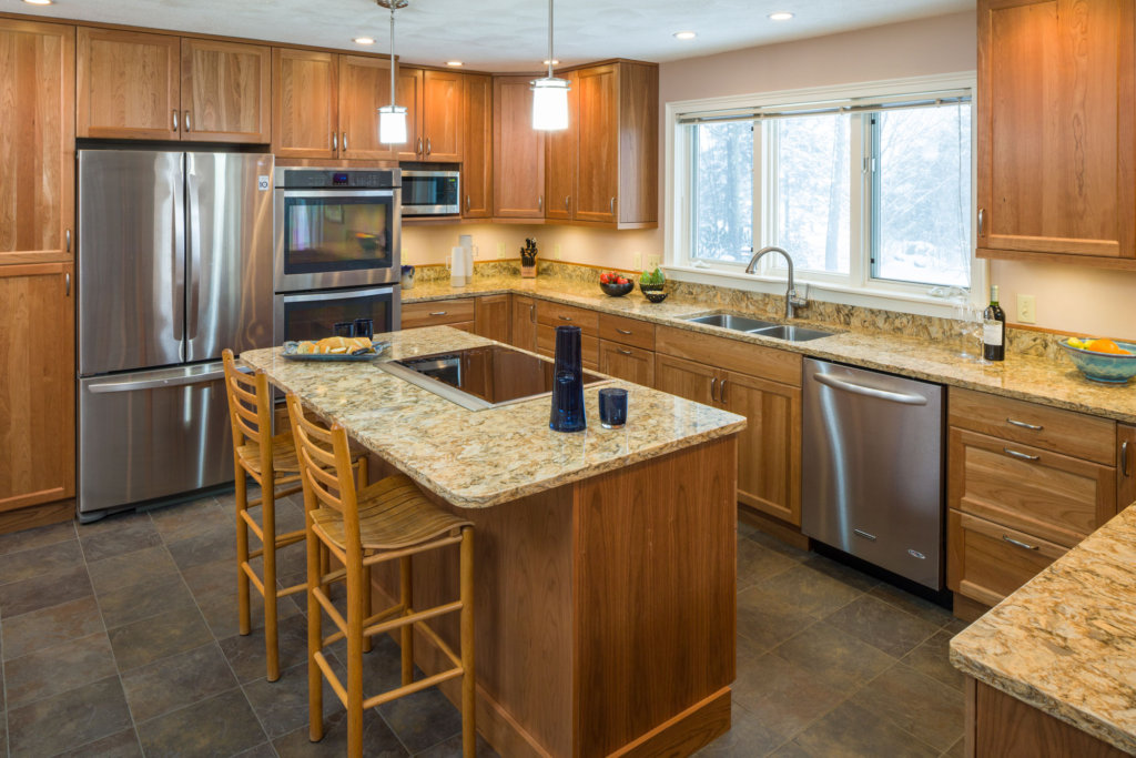 large modern kitchen scene with an island, granite countertops and a stainless steel french door refrigderator