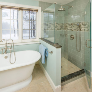 sea green bathroom scene showing a large white tube, tile shower and wintery view out a window
