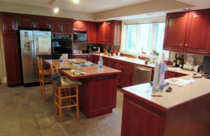 large kitchen with red-toned cabinets