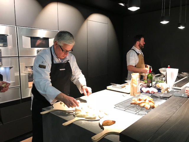 2 men at a design show preparing food