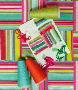 bright striped fabric from above with thread and design swatches