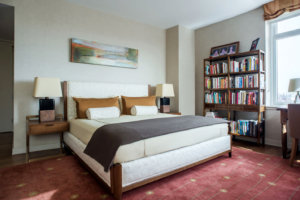 view of a bedroom with a bookshelf and maroon carpet
