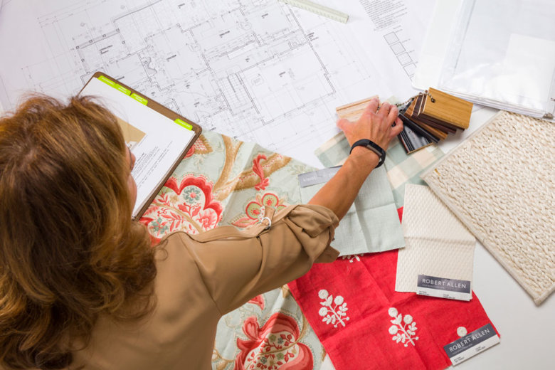female interior designer working with plans and fabric samples, view from above