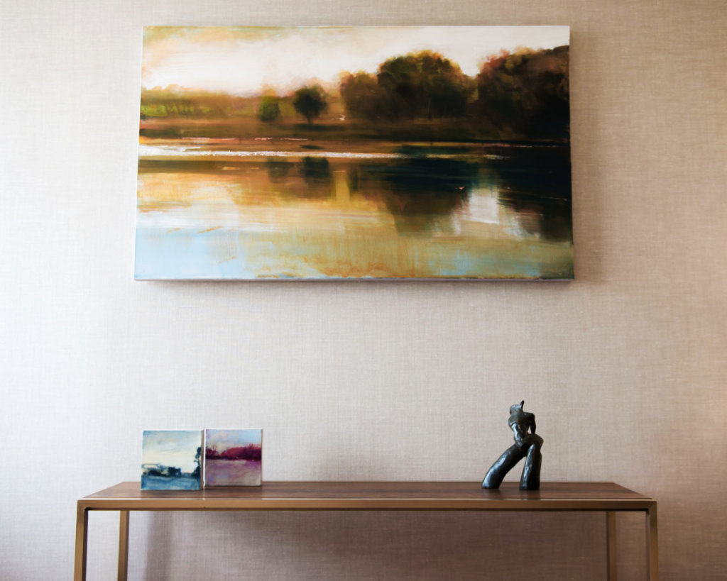 water scene painting hanging over a side table, view straight on