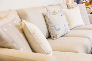 cream colored couch with throw pillows with swirls, polka dots, and sea birds