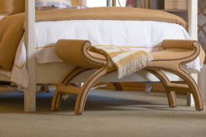 beige throw hanging over a foot stool at the end of a bed