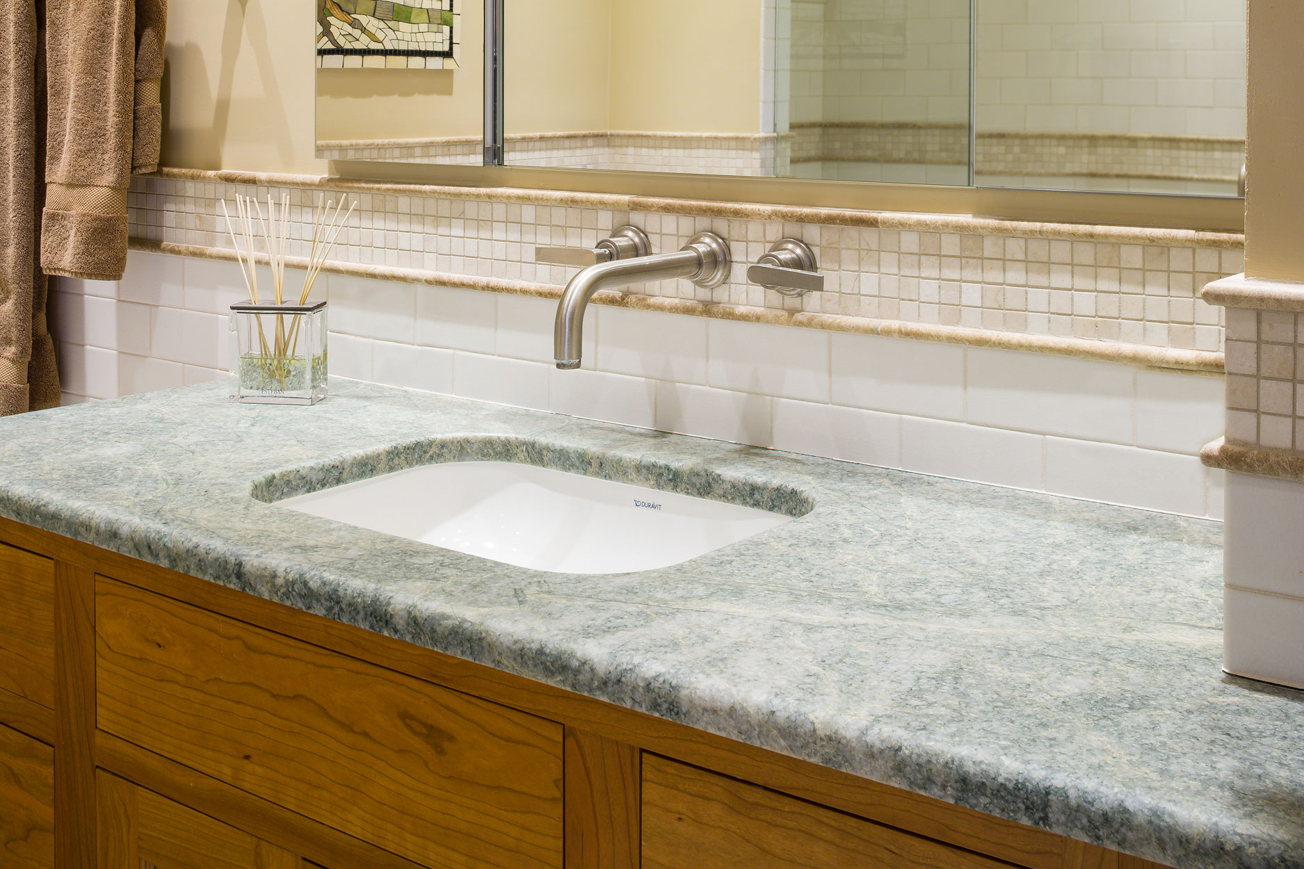 close up of a bathroom sink with a green stone countertop