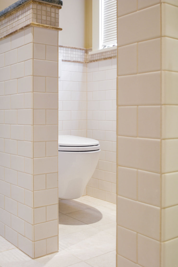 view of a modern looking toilet in a tile bathroom