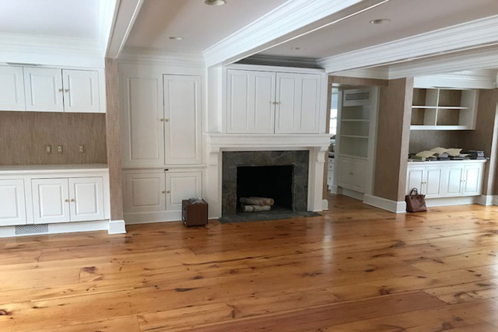 empty great room with wood flooring and white built in cabinets