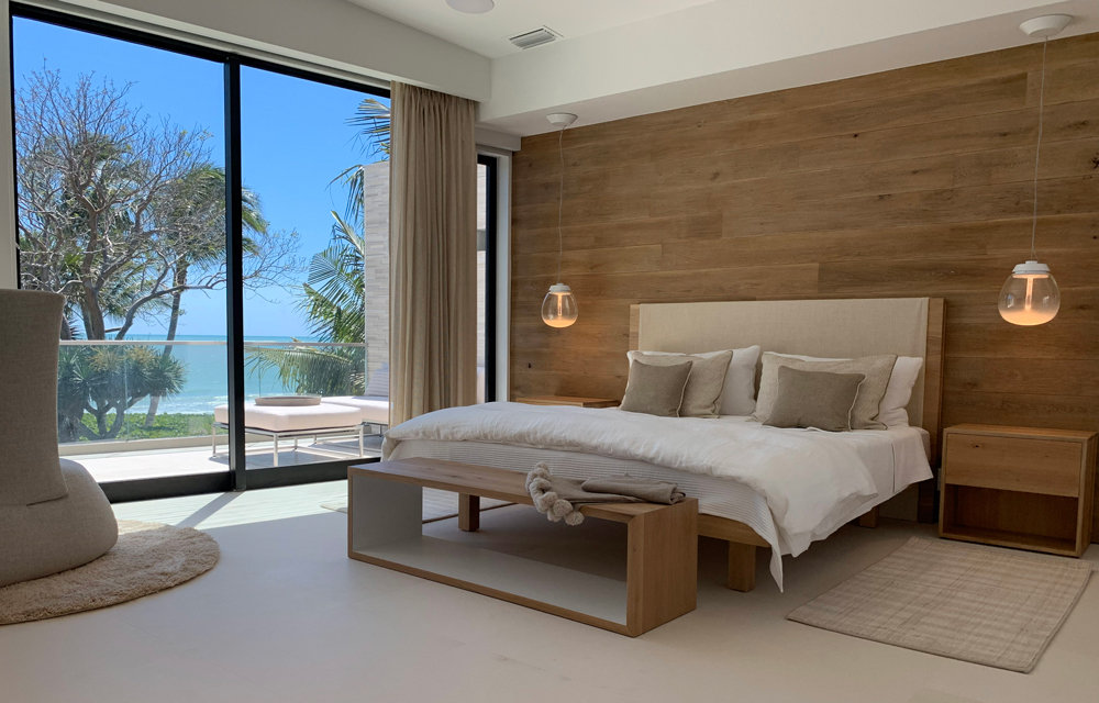 master bedroom with a full glass wall and a view of the ocean