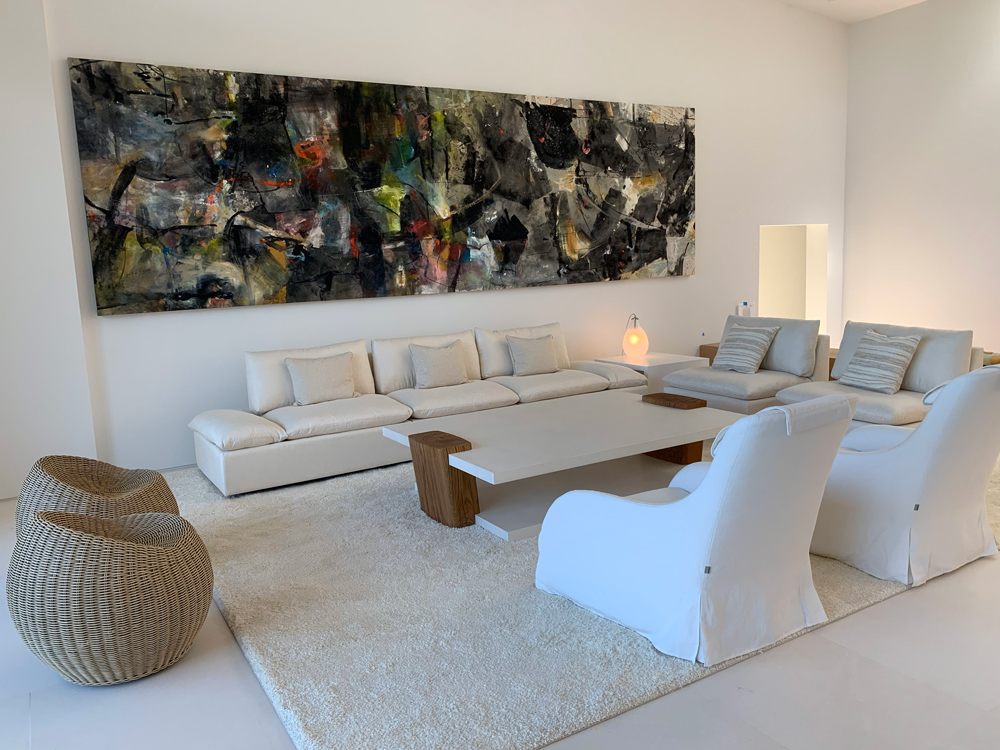 large white living room with a unique coffee table and dark panoramic painting on the wall