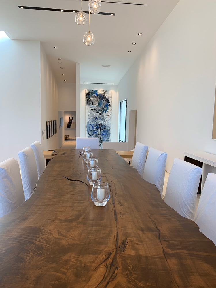 long wooden table with white chairs view from the head of the table