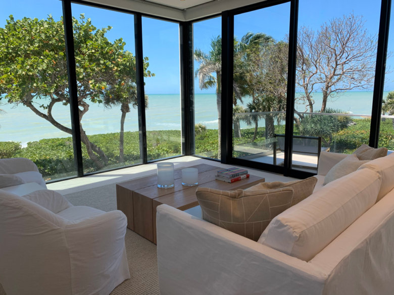 beach view from a living room with white couches and large windows